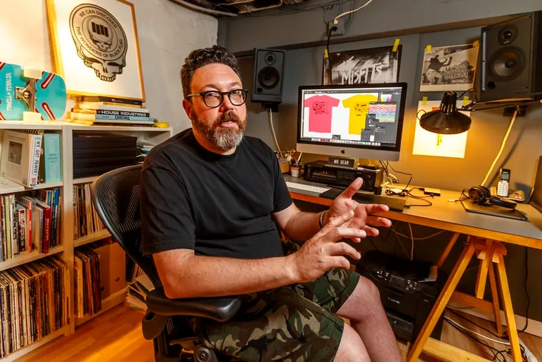 """Designer Jeremy Dean sits in his basement workspace in Montgomery County and explains how the """"Wonders of Black Flag"""" came to be. MICHAEL BRYANT / Staff Photographer"""
