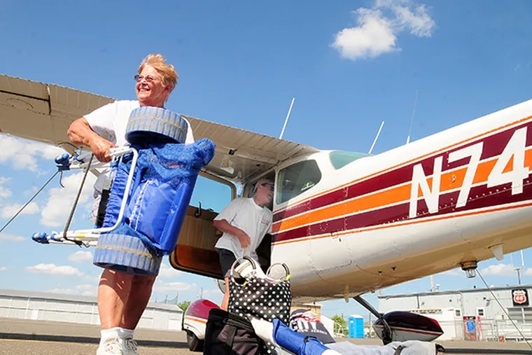 Bud and Carol Laird, from West Chester, Pa., start to load up their beach gear before heading home in their Cessna 172 Skyhawk from the Ocean City Municipal Airport in Ocean City, N.J. ( DAVE GRIFFIN / For the Inquirer )