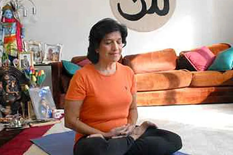 Veena Gandhi practices yoga in her Voorhees, N.J., home. The physician has a series of instructional DVDs due for release next year. ( APRIL SAUL / Staff Photographer )
