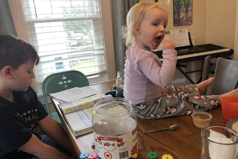 Liam Riehman-Murphy, 11, completes schoolwork while his sister Hazel, 2, sits on the dining room table. Their mother Christina, a librarian at Penn State-Abington, is juggling working remotely and supervising schoolwork for her four school-aged children during a Coronavirus-induced school break.