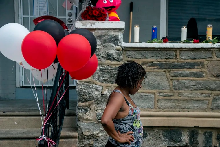 A neighbor on North Simpson Street in West Philadelphia prepares for a candlelight vigil for 7-year-old Zamar Jones.