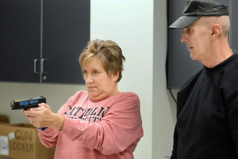 Officer Steve Dintino of East Pikeland Police (right) shows Nancy Griffith how to shoot a Glock training pistol in a shoot/don't shoot simulation during the Citizens' Police Academy at Chester County Intermediate Unit in Downingtown.