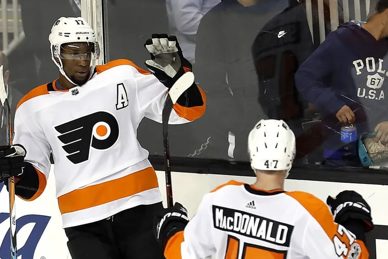 Wayne Simmonds (left) celebrates with Andrew MacDonald after completing his hat trick in the Flyers' season- opening win Oct. 4 in San Jose.