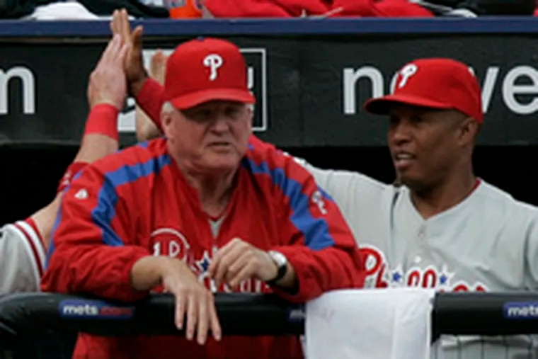 Phillies manager Charlie Manuel concentrates on the game as Aaron Rowand and hitting coach Milt Thompson high-five after Rowand scored on a throwing error in the second inning.