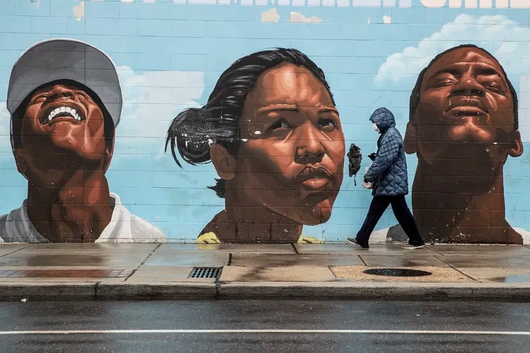 A woman wearing a surgical mask makes her way past a mural on the west side of the Save-A-Lot store at 22nd and Lehigh, where she was shopping, thats depicts many ranges of emotions on the subjects faces, on March 31, 2020.