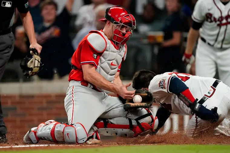 Atlanta's Travis d'Arnaud slides past Phillies catcher J.T. Realmuto to score on a double by Dansby Swanson in the fourth inning.