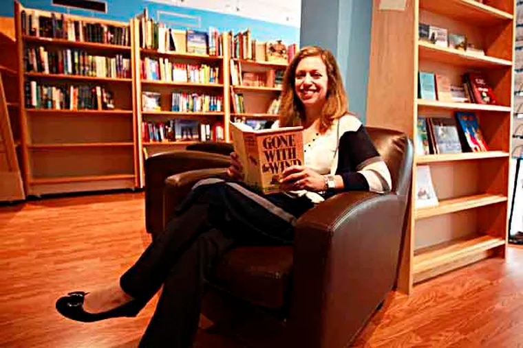 With her favorite book, Gone with the Wind, Cathy Fiebach is seated in her new book store on Lancaster Avenue in Byrn Mawr called Main Pointe Book, May 22, 2013. ( DAVID SWANSON / Staff Photographer )