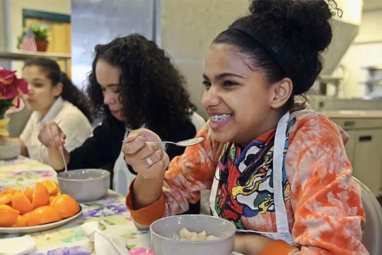 Brittany Jordan, 15 (right), samples her cereal.