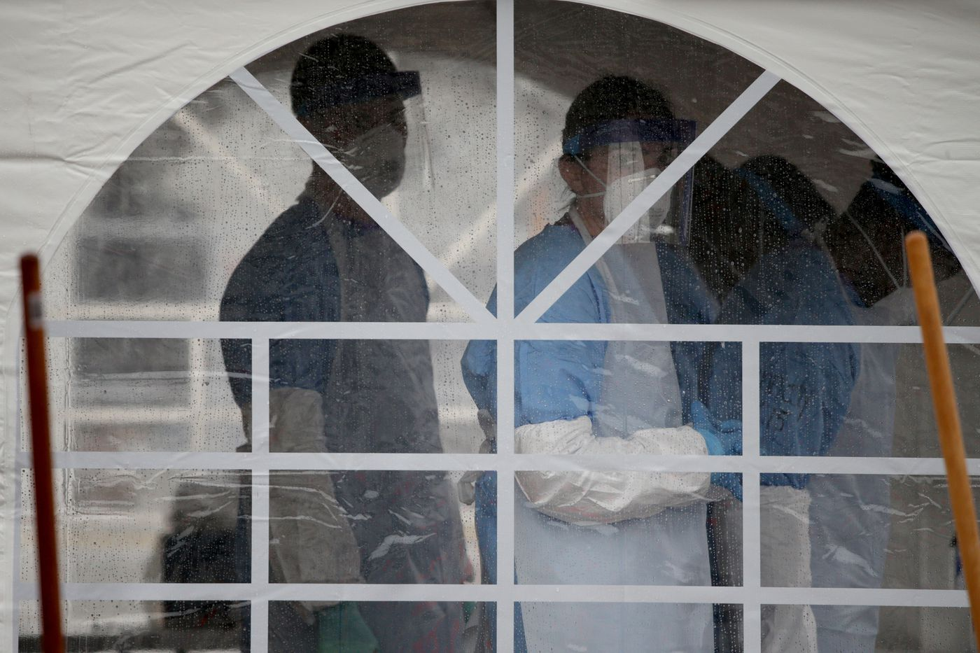 Medical workers wait in a tent at the coronavirus testing site for first responders and healthcare workers in the parking lot of the Rite Aid on the 7400 block of Ogontz Avenue in Philadelphia, PA on March 23, 2020.