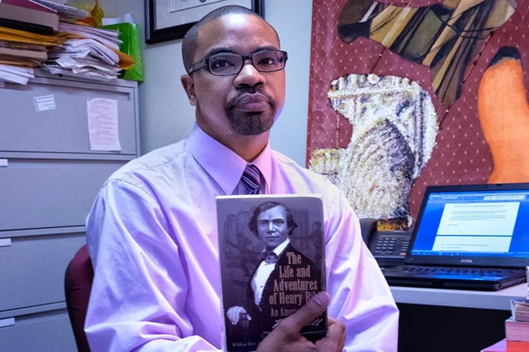 Keith Green, associate professor, researcher and author of a new book on slavery in his Rutgers-Camden office. Green has written a new book on the different variations of slavery. Henry Bibb, a slave, is a central character. (ED HILLE/Staff Photographer)