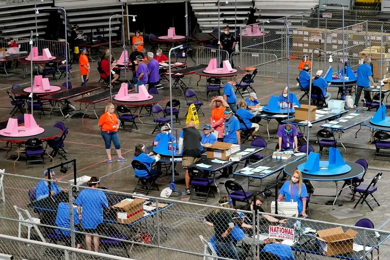 FILE - In this May 6, 2021, file photo, Maricopa County ballots cast in the 2020 general election are examined and recounted by contractors working for Florida-based company, Cyber Ninjas at Veterans Memorial Coliseum in Phoenix.