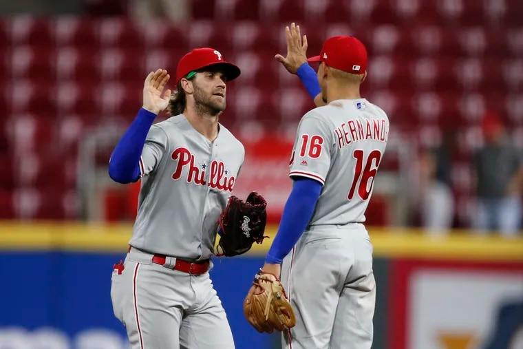 Bryce Harper, left, congratulates Cesar Hernandez after the Phillies' 6-2 victory Tuesday night in Cincinnati.