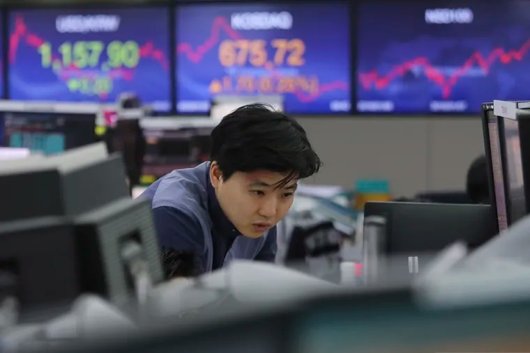 A currency trader watches monitors at the foreign exchange dealing room of the KEB Hana Bank headquarters in Seoul, South Korea, Friday, Jan. 3, 2020. Asian stocks were mixed Friday and oil prices surged after an Iranian general was killed by U.S. forces in Iraq.