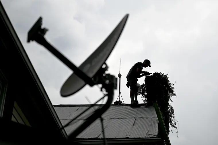 A technician installs equipment to bring broadband internet to a home in central Pennsylvania's Mifflin County. Biden's infrastructure bill could expand rural broadband.(The satellite dish is inoperable, and belonged to a previous resident.)