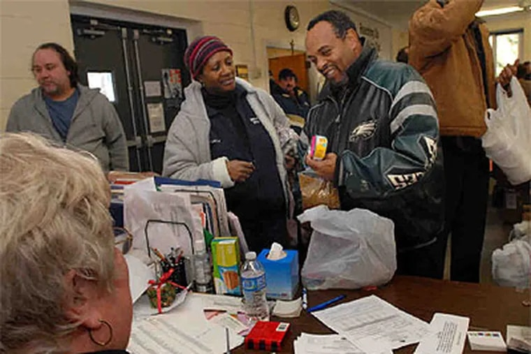 At the Loaves and Fishes Food Pantry , Linda Stone watches her friend Marvin Payne get cat food. Since August, the Prospect Park food bank, which serves 15,000 needy clients, has also been operating a second resource - for those clients' pets. (April Saul / Staff Photographer)