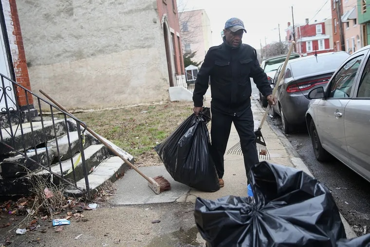 Ernest Gardner carries a bag of trash after raking it off of a vacant lot in North Philadelphia. The city has launched its pilot street-sweeping program, which will target six neighborhoods from April through November.