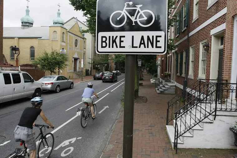 In the wake of a cyclist's death in November, advocates renewed demands for protected bicycle lanes, which include physical dividers like posts, planters, and even parked cars.