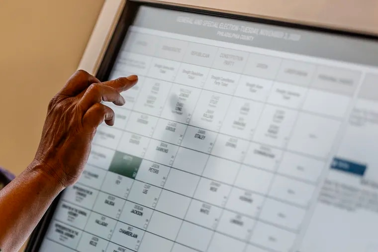 A student tries out the new voting machines that will be used in Philadelphia that were on display at the Community College of Philadelphia in September. The deal between the governor and legislature would eliminate straight-ticket voting.