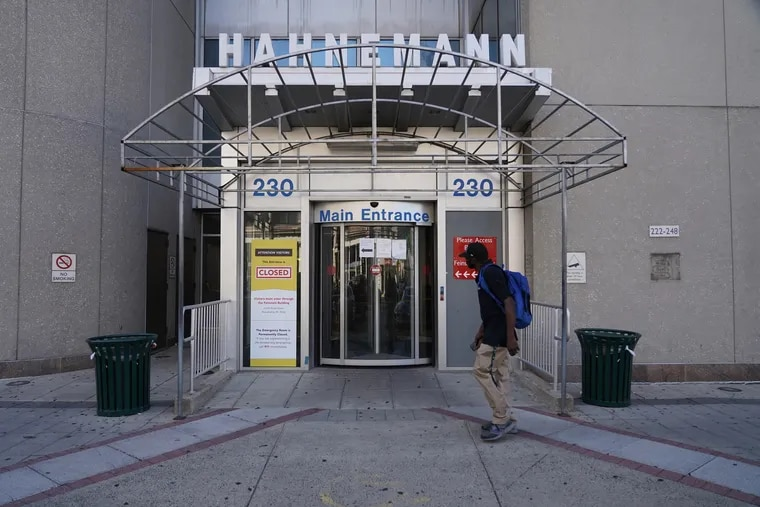 A pedestrian looking at the closed sign on the main entrance of Hahnemann University Hospital's window located at Broad and Vine Streets in Center City back in August.