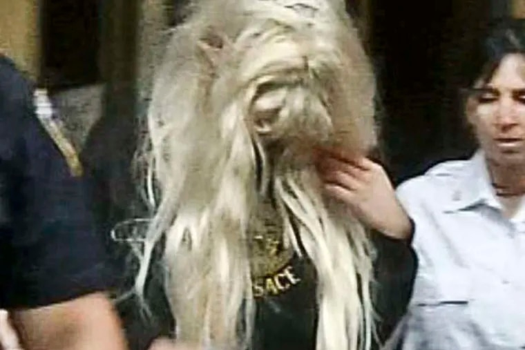 In an image made from video, actress Amanda Bynes, center, wearing sweats and a blonde wig, is escorted after a Manhattan criminal court appearance on Friday May 24, 2013 in New York.  Bynes was arrested Thursday evening and charged with reckless endangerment after police say she heaved a marijuana bong out of out of her Manhattan apartment building.  (AP Photo/APTN)