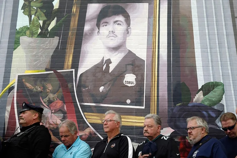 Former coworkers of slain Philadelphia police officer Daniel Faulkner stand beneath a new mural of him Monday, Nov. 24, 2014, in Philadelphia. The mural is painted on the side of the police station Faulkner worked at in the Chinatown section of the city. Daniel Faulkner was shot to death by Mumia Abu-Jamal on a downtown street in 1981. (AP Photo/Matt Rourke)