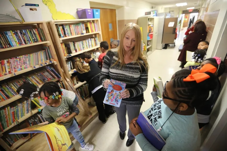 Teacher Joanne Ruiz help students check out books at the new library at Stetser Elementary.