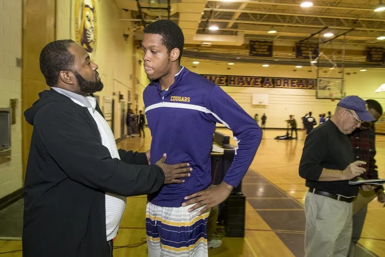 Kamal Yard talking with one of his AAU players, Martin Luther King senior Will McNair, before a recent game.