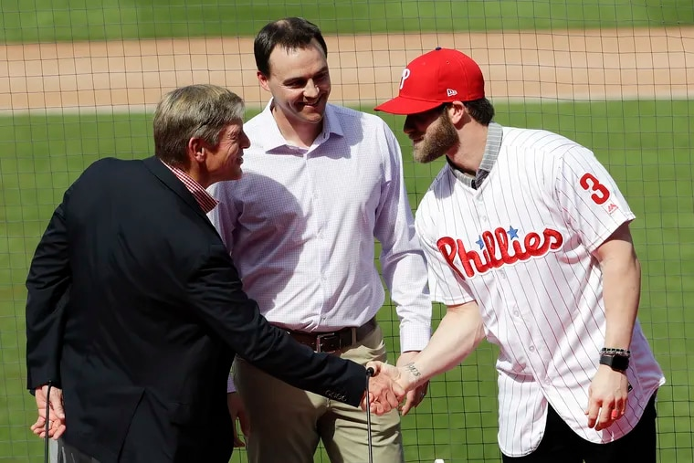 Bryce Harper shakes hands with Phillies owner John Middleton, as general manager Matt Klentak looks on, during an introductory press conference on Saturday in Clearwater.