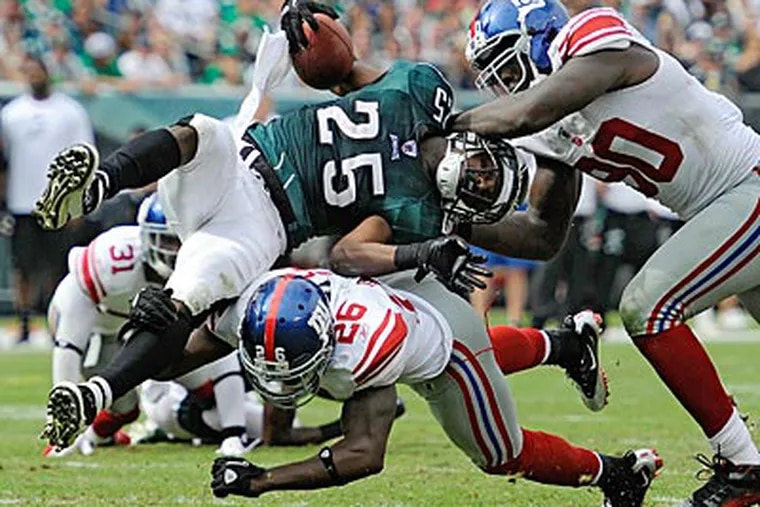 LeSean McCoy gets upended by the Giants' Antrel Rolle and Jason Pierre-Paul. (Clem Murray/Staff Photographer)
