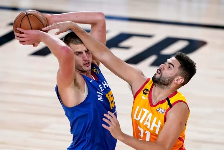 Denver Nuggets' Nikola Jokic (15) keeps the ball from Utah Jazz's Georges Niang (31) during the first half of an NBA basketball first round playoff game Sunday, Aug. 30, 2020, in Lake Buena Vista, Fla.