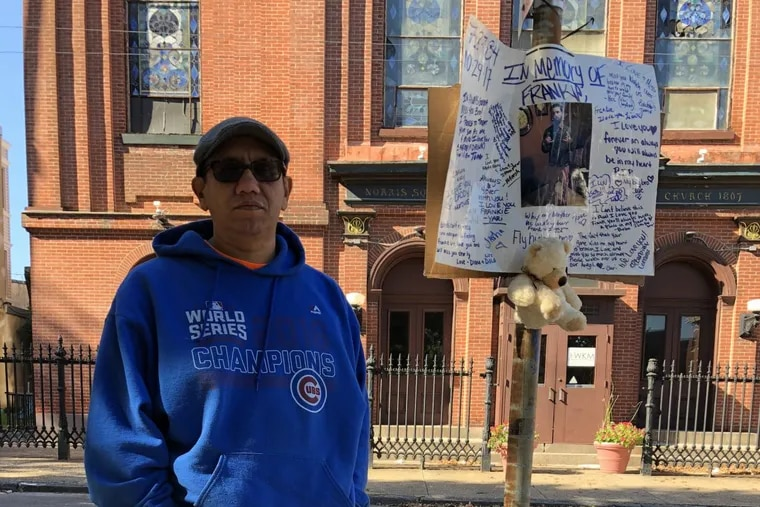 """The Rev. Adan Mairena, pastor of the West Kensington Ministry in Norris Square, stands in front of the sidewalk memorial for Francisco """"Frankie""""  Caraballo."""