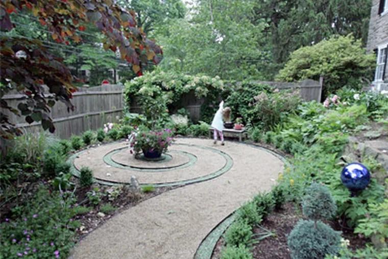 "Natalie Bauder plays in the ""Alice in Wonderland"" garden that her mother Laura created in their backyard. ( David Swanson / Staff Photographer )"