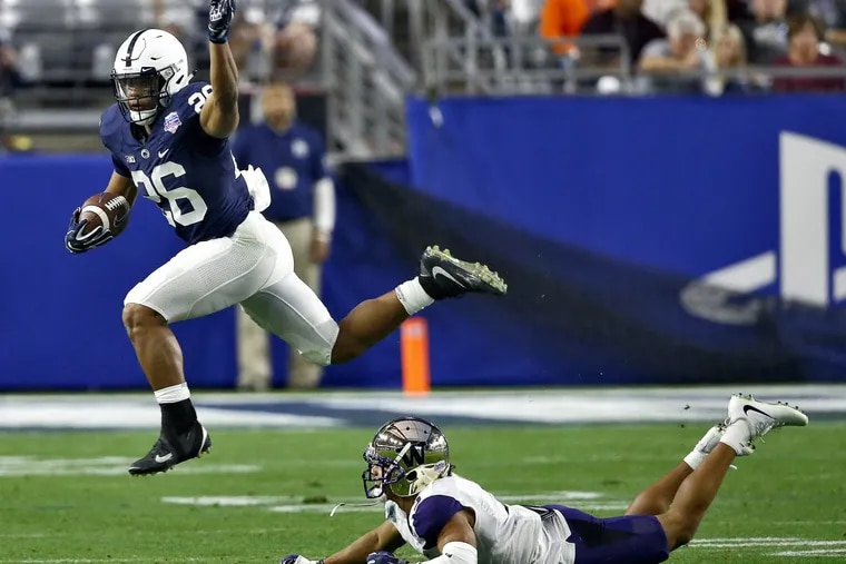 Penn State running back Saquon Barkley (left) leaps over Washington defensive back Myles Bryant during the second half of the Fiesta Bowl.