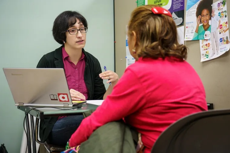 Jessy Foster, an enrollment specialist, meets with a client at an enrollment center in Philadelphia, November 5, 2018.