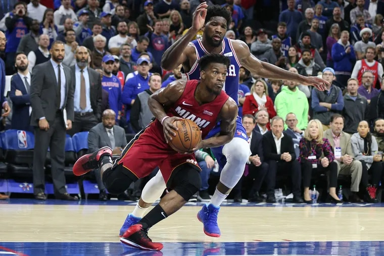 Jimmy Butler, left, of the Heat  drives by Joel Embiid of the Sixers during the fourth quarter.