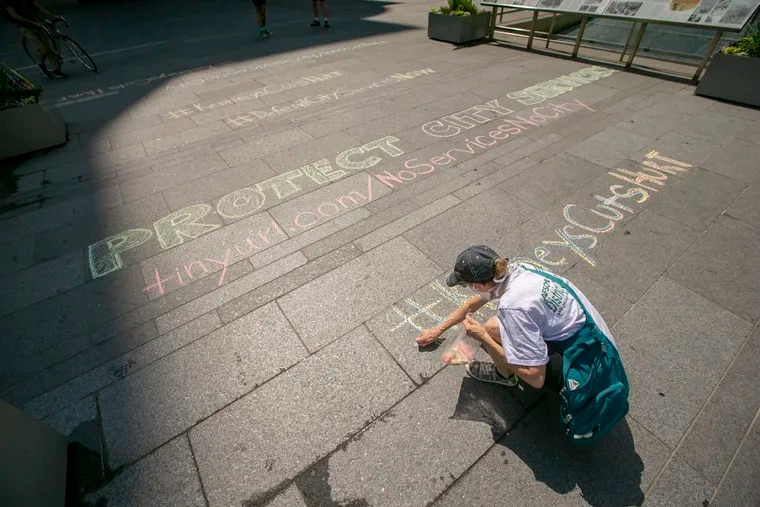 """Abbey Klebanoff, member of District Council 47, chalks a message on Dilworth Plaza before the start of a rally, """"Day of Action for a Just Philly Budget,"""" on Tuesday."""