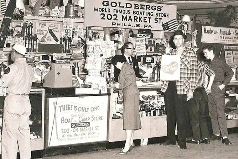 Charles Goldberg, behind the counter, at the Philadelphia Sportsmen's Show in 1958. After World War II, he and his older brothers formed Goldbergs' Marine, selling boating equipment from a Market Street store.