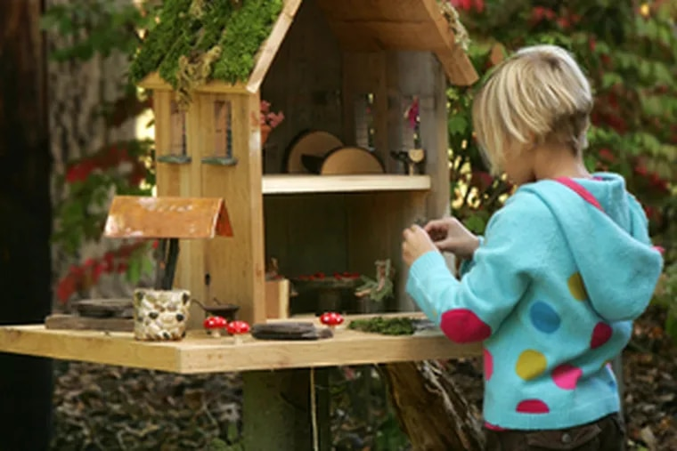 Grace Wyszynski, 51/2, of West Akron, Ohio, plays with the fairy house fashioned of cedar by her parents. On an island in Maine, building fairy houses is a local tradition.