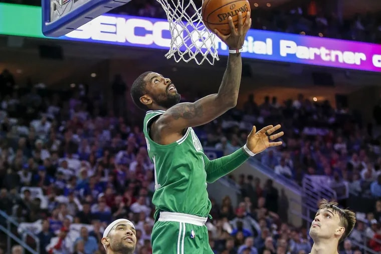 Celtics guard Kyrie Irving lays up the ball past Sixers guard Jerryd Bayless (left) and forward Dario Saric during the teams' first meeting this season.
