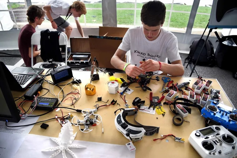 """Sixteen year-olds Kevin Fallon (at table), Sam Weissman (rear, left) and Nolan Gelinas work on their drones as part of the """"Kwad Squad,"""" a group of Philadelphia and New Jersey suburban high school classmates and family friends. Drone laws may expand this year to allow for remote flight."""