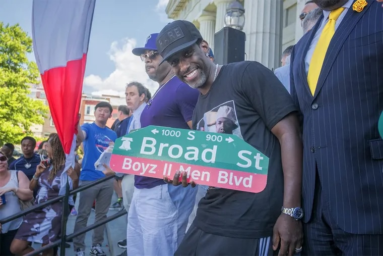 "Boyz II Men band member Shawn Stockman shows off a new street sign proclaiming part of Broad Street ""Boyz II Men Blvd."""
