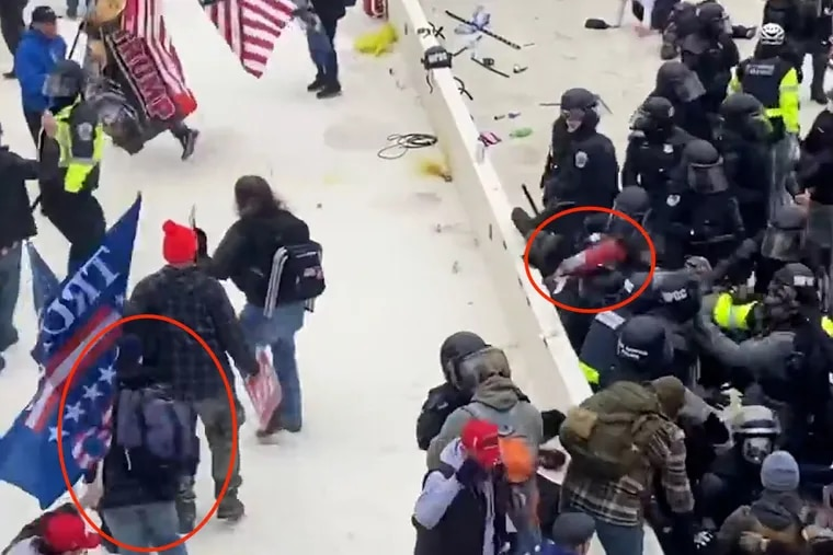 A freeze frame image shows a fire extinguisher landing on a group of police officers during the insurrection at the U.S. Capitol on January 6, 2021. Prosecutors said Robert Sanford, a former Chester, Pa. firefighter, injured three people when he tossed the extinguisher at the head of an officer.