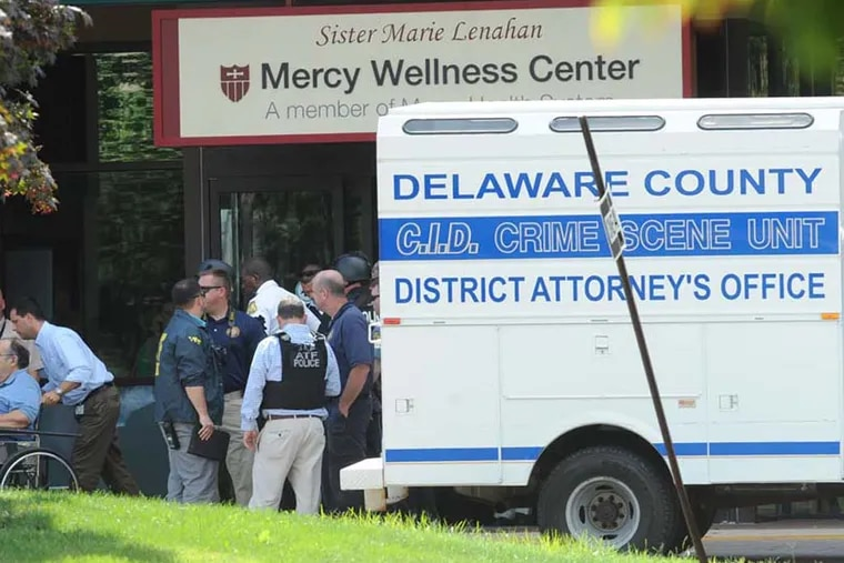 A patient leaves the Mercy wellness center after a shooting incident that left a woman dead and two men wounded. ( CLEM MURRAY / Staff Photographer )