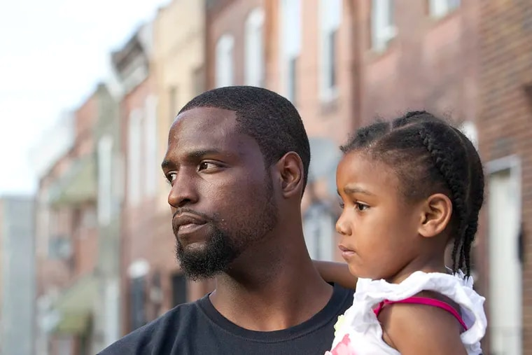 Tyrique Glasgow stands at Tasker and Taney Streets with his daughter, Ty'ana Glasgow, 3. ( CHARLES FOX / Staff Photographer )