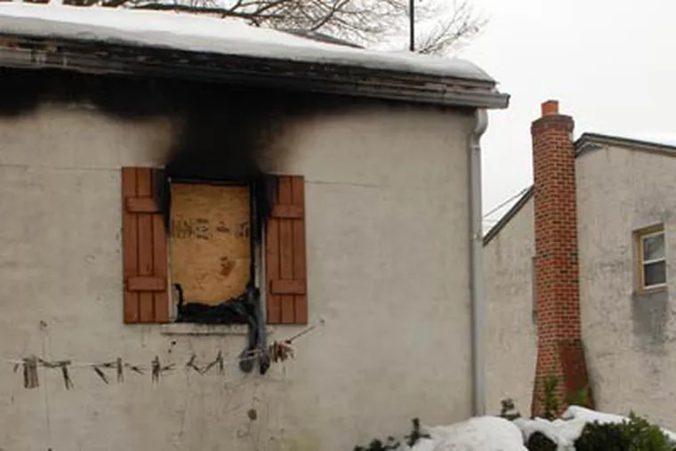 Evidence of the Christmas morning fire that took the life of Sandra Hardwick streaks the outside wall of her Cherry Hill home. (Tom Gralish / Staff Photographer)