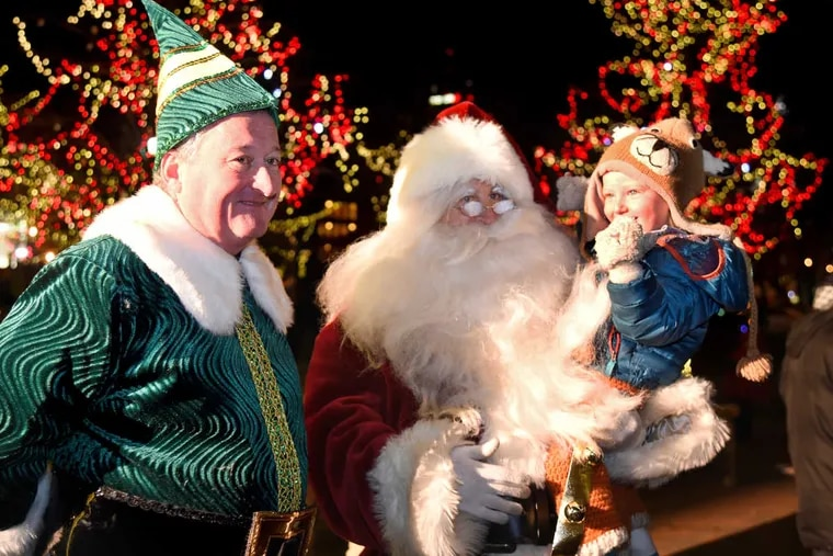 Mayor  Kenney as Buddy the Elf and Councilman Mark Squilla as Santa, with 3-year-old Miles Zamechek in Franklin Square.