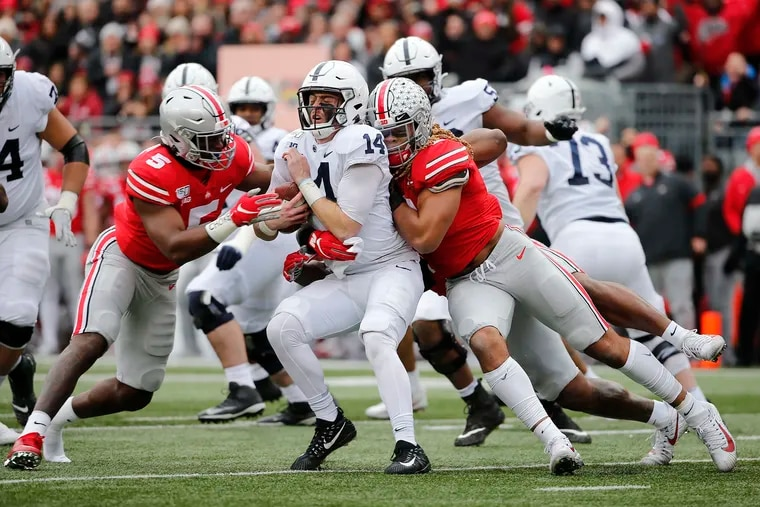 Ohio State defensive end Chase Young (2) and linebacker Baron Browning (5) sack Penn State quarterback Sean Clifford during the first quarter.