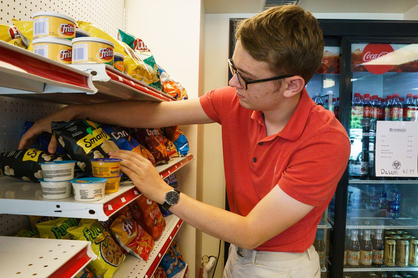 Tyler Haney, a senior in the autism program, arranges stock at the Ram Store.