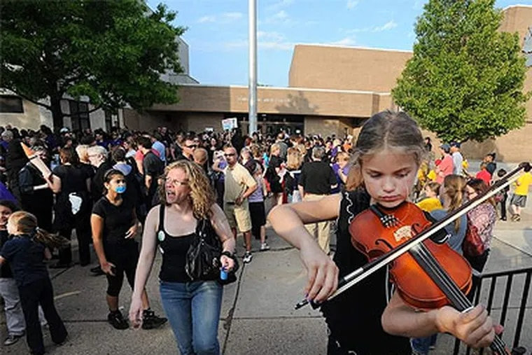 Ava Cooley, 9, plays her violin to a crowd of more than 500 protesters outside Upper Darby High School before a school board meeting. Cuts are expected to be made to the arts, foreign language, music, technology, and other programs. (Sharon Gekoski-Kimmel / Staff Photographer)