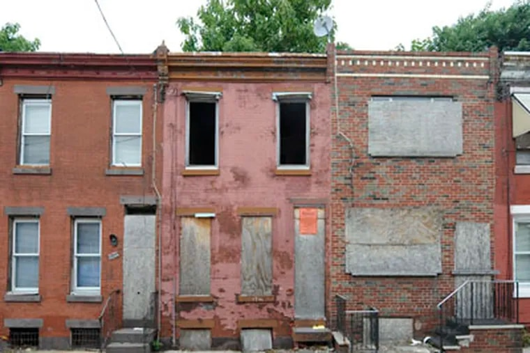"""Abandoned houses, like these on Gerritt Street in South Philadelphia, hurt the value of others nearby, but the city's ineffectiveness at seizing them for back taxes leaves them festering, sometimes for many years. <a href="""" http://www.philly.com/philly/news/special_packages/inquirer/126266183.html?cmpid=124488749""""><b>Click here for a map of delinquent properties.</b></a> (Clem Murray / Staff Photographer)"""